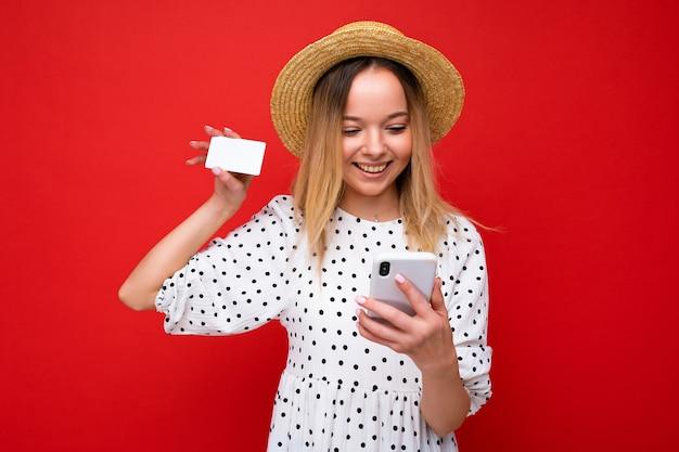 Фото веселой симпатичной блондинки в летнем наряде, использующей мобильный телефон и держащей кредитную карту