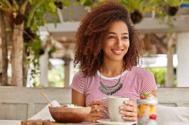 巻き毛の陽気なリラックスした黒人の女の子の写真、コーヒーのマグカップを保持し、娯楽を楽しんで、エキゾチックなカフェテリアを訪問し、海外で夏休みを過ごし、脇を見る