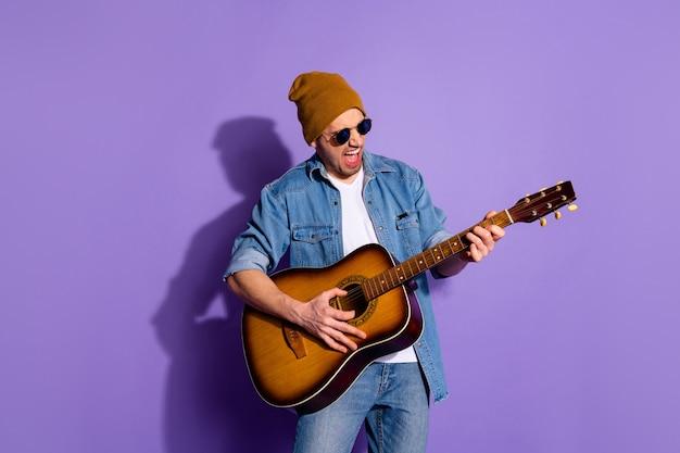 보라색 생생한 컬러 배경 위에 절연 안경을 착용하는 음악가 악기를 연주 손으로 기타를 들고 모자를 쓰고 쾌활한 무례한 매력적인 잘 생긴 남자의 사진