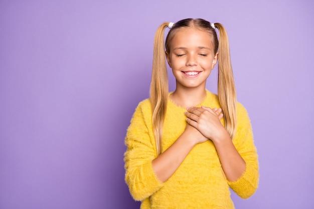 笑顔の歯が孤立したパステルバイオレット色の壁の下にハートと胸に手を置く陽気な穏やかな金髪の陽気なカジュアルな穏やかな女の子の写真