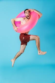 Фотография веселого туриста без рубашки в резиновом кольце, улыбающегося во время прыжков и дайвинга