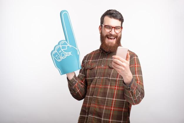 Фото веселый улыбающийся молодой человек, глядя на смартфон и держа веер пены перчатки