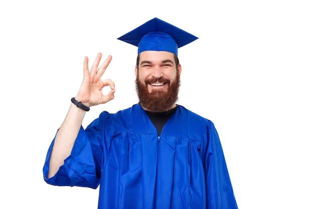 卒業して大丈夫なジェスチャーを示している陽気な学生男性の写真