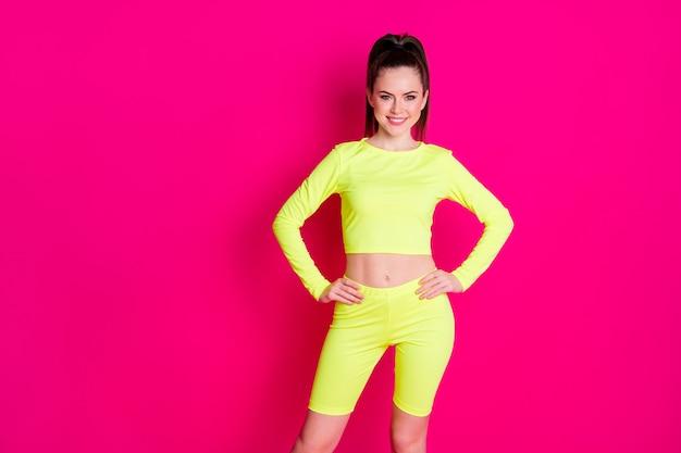 Фото веселой сладкой молодой женщины, одетой в спортивную одежду, руки, руки, талию, изолированные на розовом цветном фоне