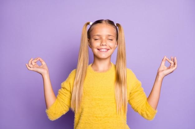 Фотография веселой зубастой сияющей девушки, медитирующей и занимающейся йогой, изолирована в пастельных тонах на фиолетовой стене