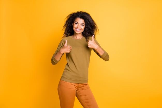 Фотография веселой модной милой очаровательной подруги показывает вам два больших пальца вверх в брюках, изолированных на ярко-желтом фоне