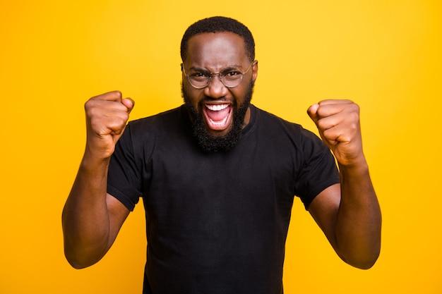 Tシャツの眼鏡で孤立した鮮やかな色の壁の顔に幸福の失礼な感情を表現する陽気なトレンディな叫び声の男の写真
