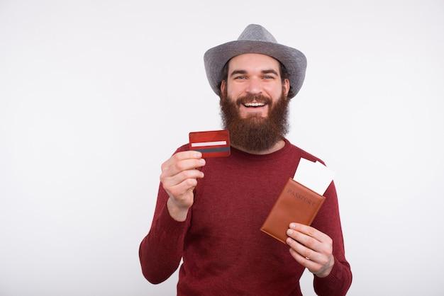 パスポートチケットとクレジットカードを保持している陽気な若いひげを生やした男の写真