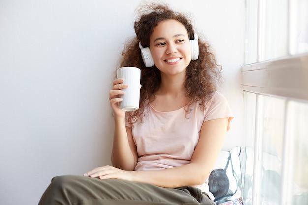 窓際に座ってお茶を飲み、ヘッドフォンでクールな音楽を聴き、家で晴れた日を楽しんでいる陽気な若い巻き毛のムラートの女性の写真。