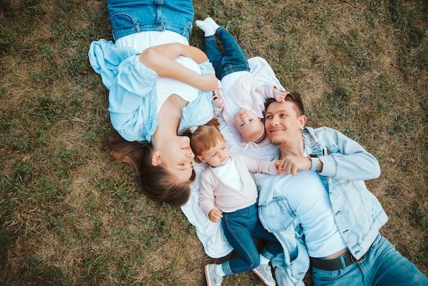 公園、家族の時間の芝生の上に屋外で横たわっている赤ちゃんの子供たちと陽気な若い家族の写真