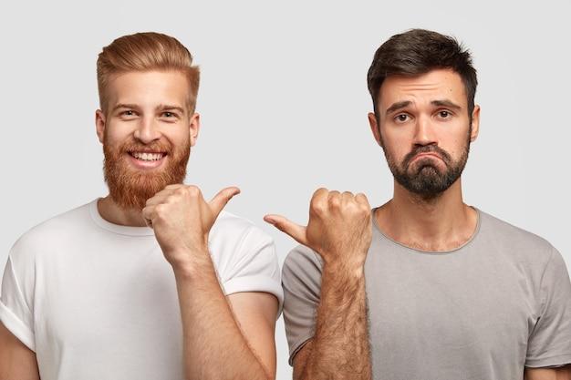 陽気な若い生姜男と不機嫌な無精ひげを生やした白人男性がお互いに親指を向けて、白い壁に隔離されたチームとして一緒に働く写真。友情と感情の概念