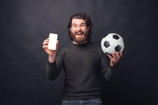 Фото веселого молодого красивого бородатого мужчины, держащего футбольный мяч и показывающего пустой экран на смартфоне