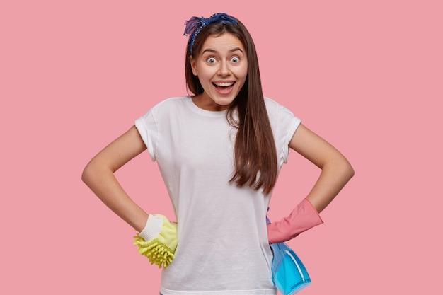 На фото веселая молодая горничная держит руки на талии, носит повседневную белую футболку, повязку на голову, защитные перчатки.