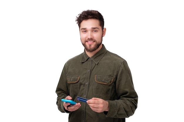 신용카드와 스마트폰을 들고 흰색 백고펀트 너머로 카메라를 바라보는 쾌활한 젊은 남자의 사진