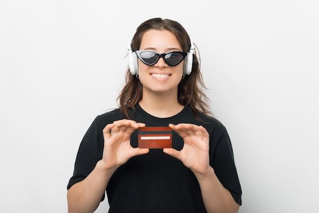 선글라스를 착용하고 빨간 신용카드를 보여주는 쾌활한 젊은 트렌디한 여성의 사진