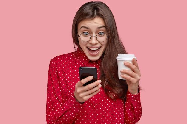 Фотография веселой молодой женщины проверяет социальные сети, играет в игры по телефону, просматривает онлайн-приложения, пьет кофе на вынос, одетая в красную одежду