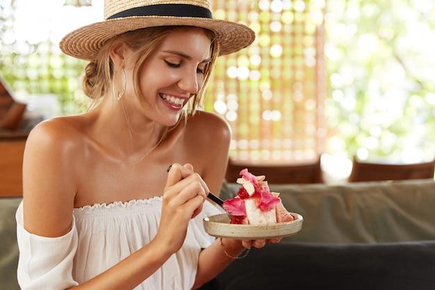 Фотография жизнерадостной молодой женщины в соломенной летней шляпе и белой блузке, ест вкусный торт в ресторане, довольная хорошим обслуживанием, приятно с кем-то беседует, радостно смеется
