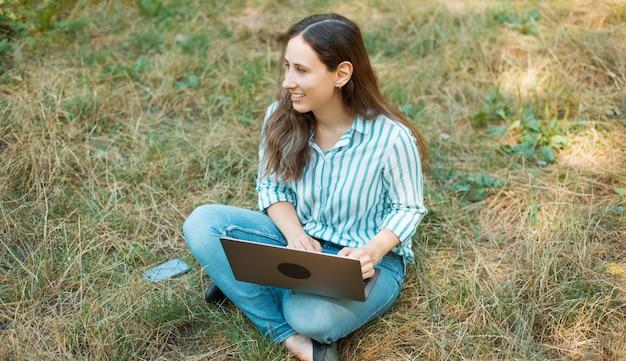 公園のグラの上に座ってラップトップを使用して陽気な若い女性の写真。