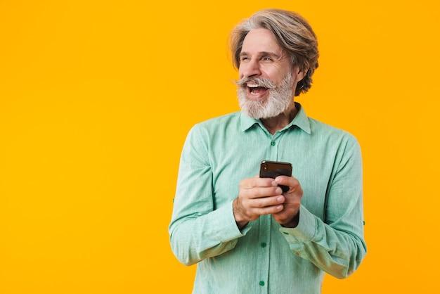 Фотография веселого позитивного седого бородатого мужчины в синей рубашке позирует изолирована на желтой стене с помощью мобильного телефона, глядя в сторону.