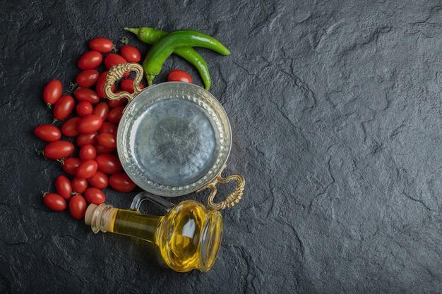 Фотография помидоров черри, сковороды с зеленым перцем и бутылки с маслом. фото высокого качества