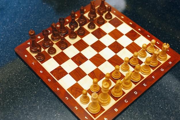Фотография шахматной доски над каменным черным столом, готовым к игре