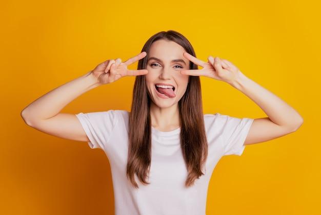 두 개의 v 표시가 눈을 덮는 유치한 여성의 사진은 혀가 노란색 배경에 포즈를 취한 흰색 티셔츠를 입고 있음을 보여줍니다.