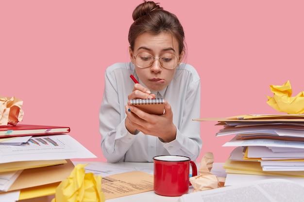 영리한 호기심 많은 젊은 여성의 사진은 메모장에 기록하고 펜을 세 심하게 잡고 큰 안경과 흰색 셔츠를 입고 기록을 만듭니다.