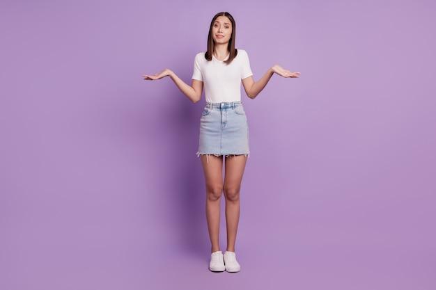 Фото невежественной неуверенной неуверенной дамы пожимает плечами и смотрит в камеру на фиолетовом фоне