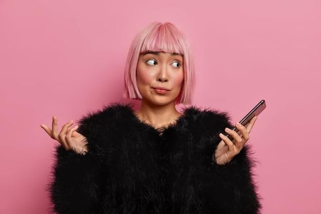Фотография невежественной молодой женщины с розовыми волосами каре смотрит в сторону и чувствует, что нерешительно пожимает плечами, держит мобильный телефон не знает, в какое время происходит встреча, носит теплый черный пушистый свитер, позирует в помещении