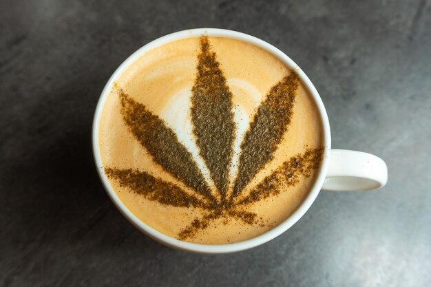 Фотография кофе в кружке с листом каннабиса на вершине.