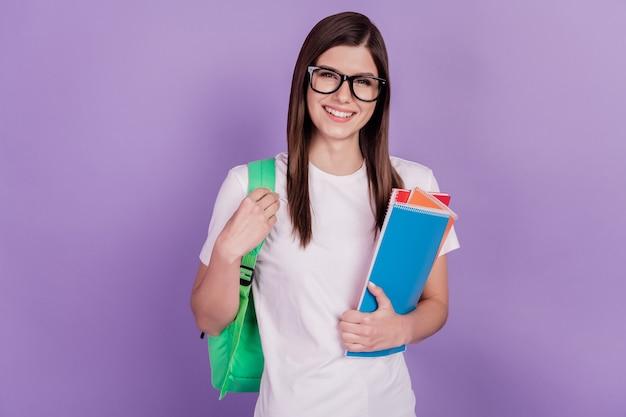 대학생 소녀의 사진은 카피북 가방을 들고 보라색 배경에 고립되어 있습니다.