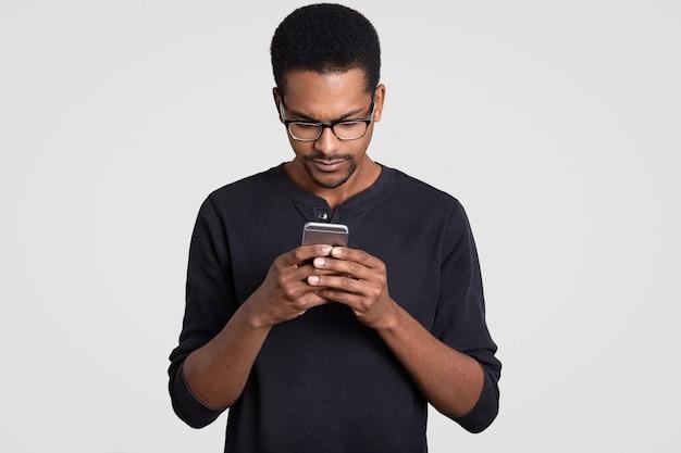 Фотография сосредоточенного темнокожего красавца читает новости в интернете, держит мобильный телефон, носит прозрачные очки и свитер
