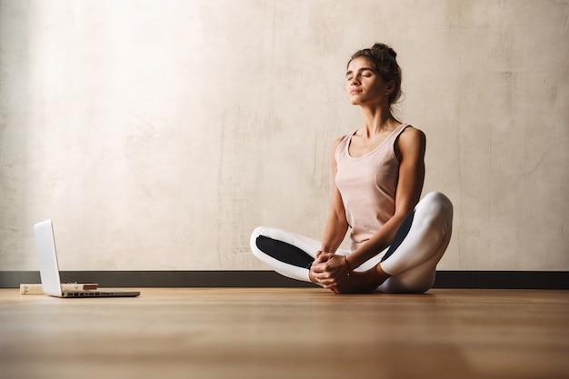 Фотография сосредоточенной красивой женщины в спортивной одежде, делающей упражнения с закрытыми глазами и использующей ноутбук, сидя на полу дома