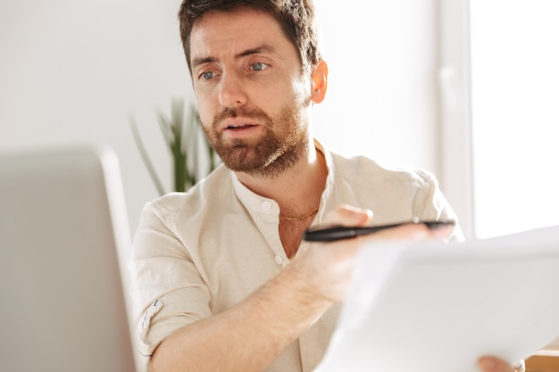 Фотография сосредоточенного офисного работника 30-х годов в белой рубашке с ноутбуком и бумажными документами, сидящего за столом на современном рабочем месте