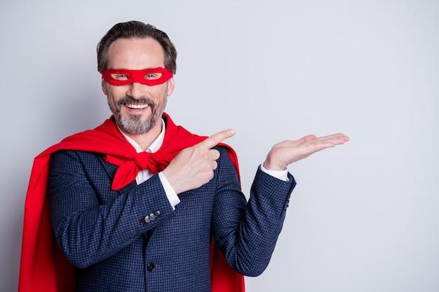 Фотография уверенного в себе пожилого делового парня, костюм супергероя, прямые пальцы, открытая рука, держать новинка, продукт, пустое пространство, предложение, носить костюм, красный плащ с маской для лица, изолированный серый фон