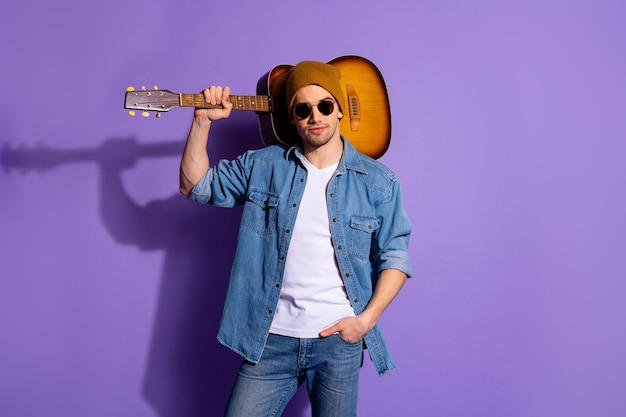 보라색 생생한 컬러 배경 위에 절연 주머니에 그의 어깨와 손에 기타와 함께 서 갈색 모자 안경을 쓰고 자신감이 매력적인 잘 생긴 남자의 사진