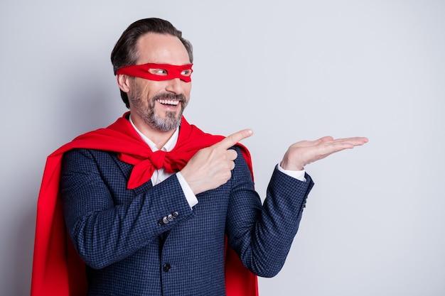 Фотография уверенного в себе жизнерадостного пожилого делового парня, костюм супергероя, прямые пальцы, открытая рука, новинка, продукт, пустое пространство, предложение, одежда, костюм, красный, маска для лица, плащ, изолированный серый фон
