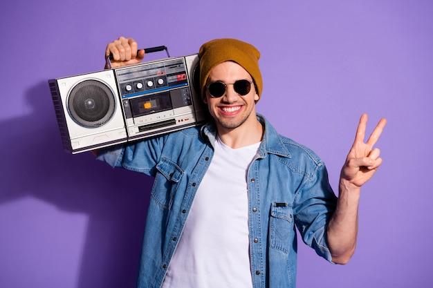 보라색 생생한 컬러 배경 위에 절연 흰색 티셔츠를 입고 손으로 레트로 레코더를 들고 이빨 웃고 v 기호를 보여주는 자신감 쾌활한 친절한 친절한 남자의 사진