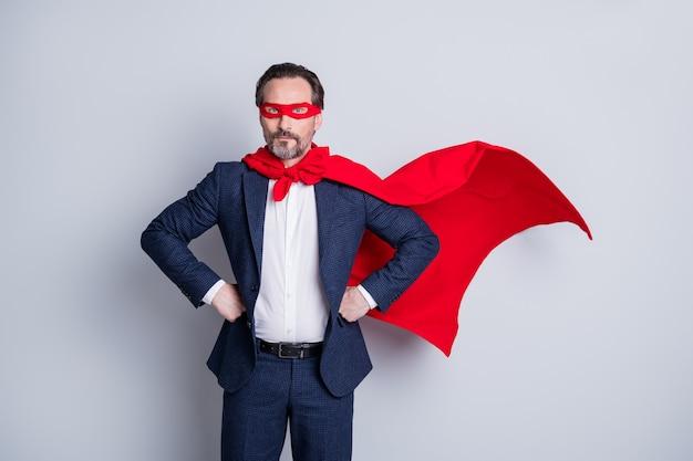 Фото уверенного мужества профессионального зрелого делового парня с оружием в руках корпоративная вечеринка костюм супергероя персонаж носит синий костюм красный плащ с маской для лица изолированный серый фон
