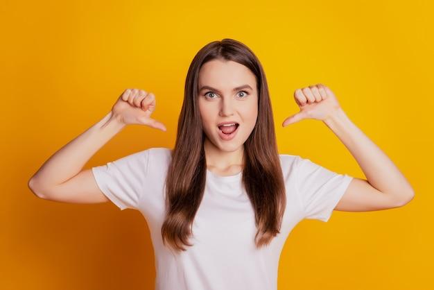自信を持って自己中心的な女性の写真は、親指自身が黄色の背景にポーズをとっている白いtシャツを着ていることを示しています