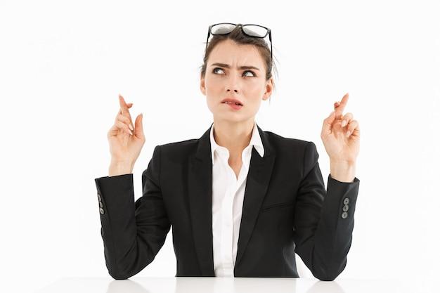 白い壁に隔離されたオフィスの机に座って仕事をしながら、指を交差させて正装を着た自信のある女性労働者の実業家の写真