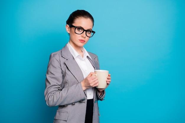 Фотография уверенной в себе девушки-финансиста, держащей чашку горячего капучино, в сером пиджаке, изолированном на синем цветном фоне