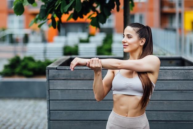 物理的なトレーニングの前に腕を伸ばしてランニング服を着た自信のある若いスポーツウーマンの写真。