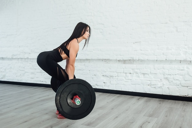 Фото уверенно молодой женщины, делающей тяжелую тренировку в спортзале, возвращаясь.