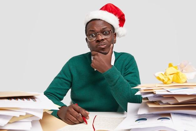 Фото смущенного темнокожего задумчивого мужчины, держащего рукой подбородок, думающего о бухгалтерском отчете, записывает информацию в блокнот