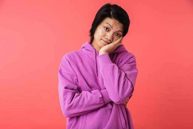 Фотография удовлетворенного азиатского парня в толстовке, улыбающегося рукой на лице, изолированного над красной стеной