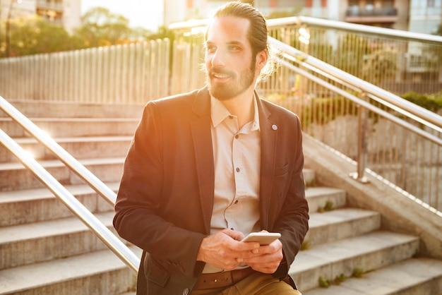 Фотография довольного делового мужчины 30-х в строгом костюме, держащего сотовый телефон и печатающего на клавиатуре, стоя на лестнице в городской местности