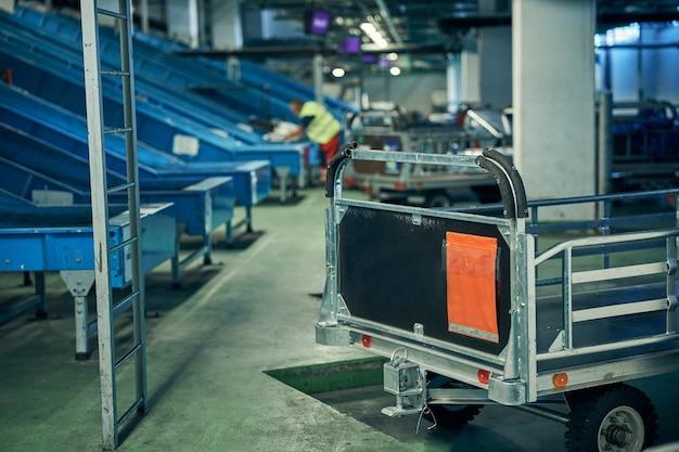 空港の手荷物取り扱いエリアでの手荷物仕分け用コンベヤーベルトと輸送用トロリーの写真