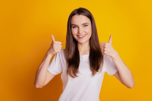 Фото крутой жизнерадостной дамы поднимают два больших пальца вверх, зубастая улыбка в белой футболке позирует на желтом фоне