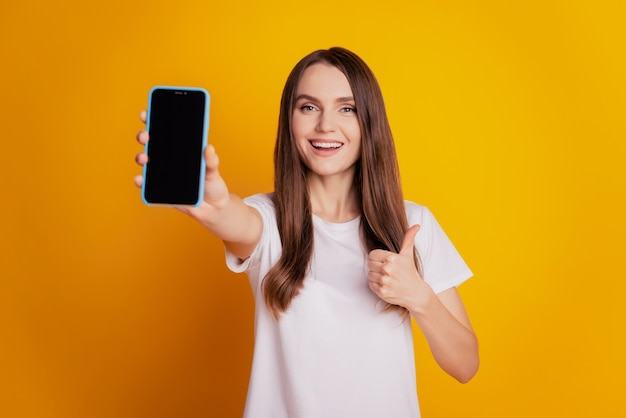 クールな女性のショー電話のタッチスクリーンの空きスペースの写真は、黄色の背景にポーズをとって親指を立てる白いtシャツを着る